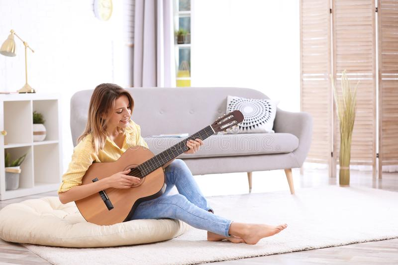Young woman playing acoustic guitar in room. Young woman playing acoustic guitar in living room stock image