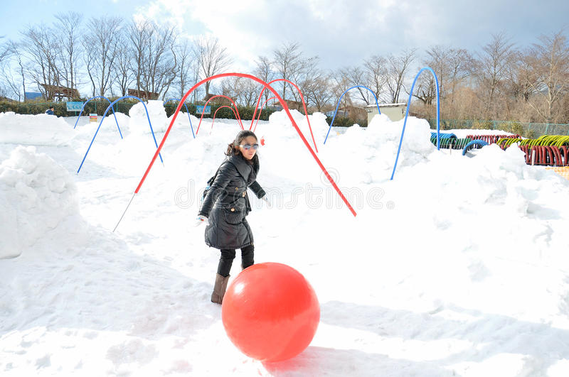 Young woman playing ball on the snow stock image