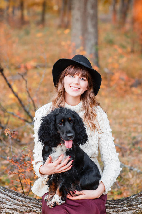 Young woman playing with black puppy in the autumn forest stock images