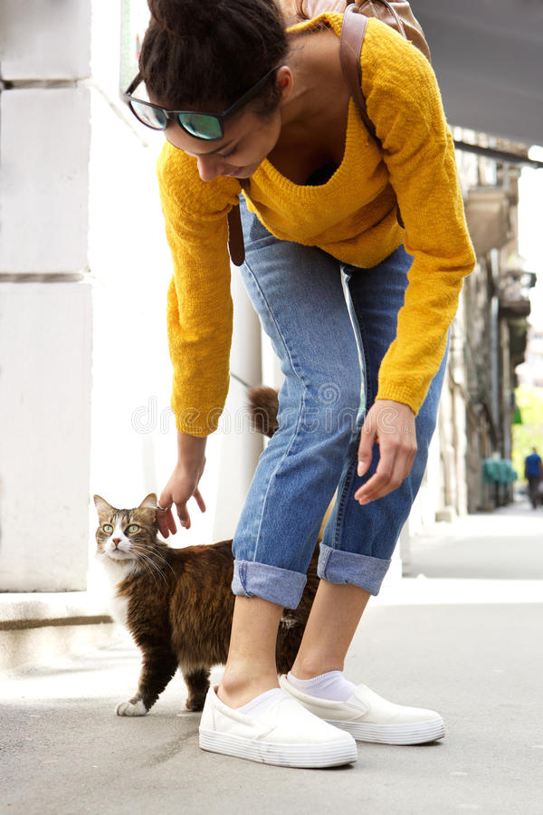 Young woman playing with a cat on city street stock image