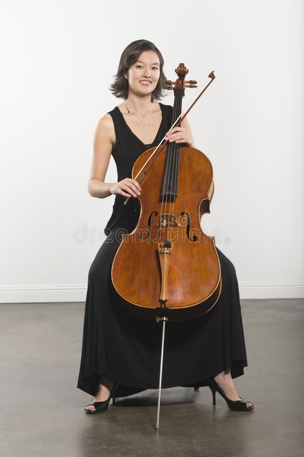 Young Woman Playing Cello. Portrait of a beautiful young woman playing cello against white wall royalty free stock photo