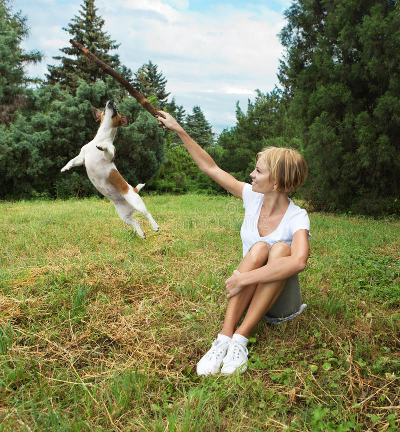 Young woman playing with dog. Happy young woman playing with dog in park royalty free stock image