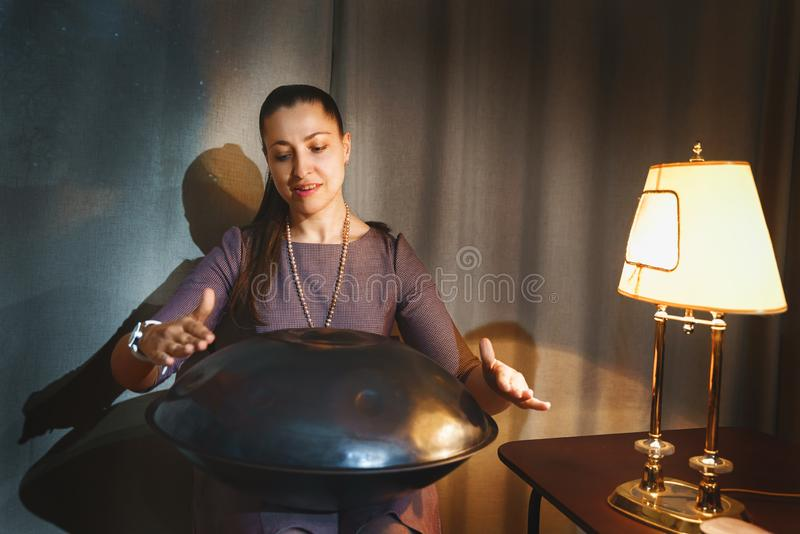 Young woman playing on a first generationan instrument called `` Hang `` or ``Hang drum royalty free stock photo