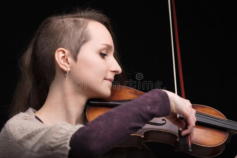 Young woman playing folk violin. Young woman with half of her hair shaved while playing a baroque violin on a black background royalty free stock image