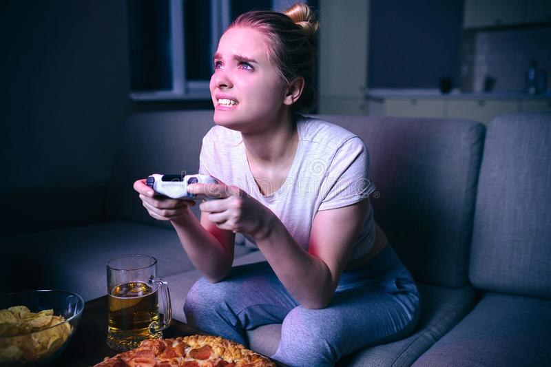 Young woman playing game at night. Worried model playing intensive game. Hold console in hands and look forward. Playing stock photos