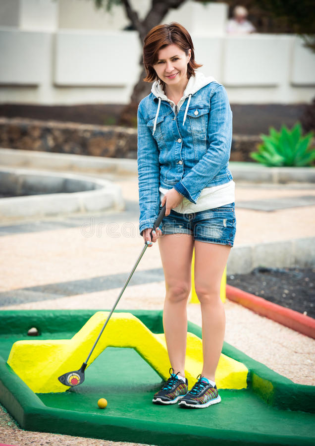 Young woman playing golf stock photography