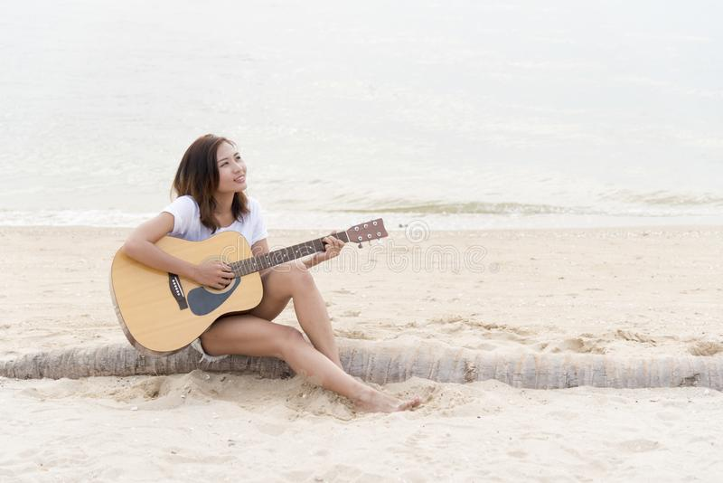 Young woman playing guitar on the beach. Musician lifestyle. Travel concept royalty free stock photography