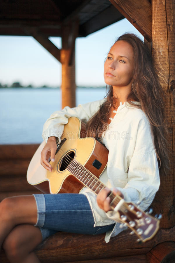 Download Young Woman Playing Guitar Outdoor On Sunset Stock Photo - Image: 10996672