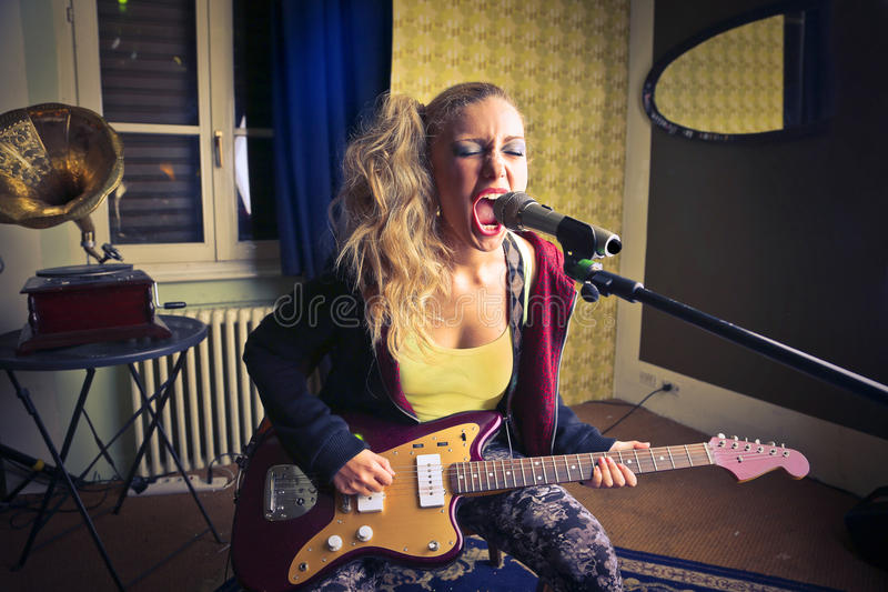 Young woman playing the guitar and singing royalty free stock photos