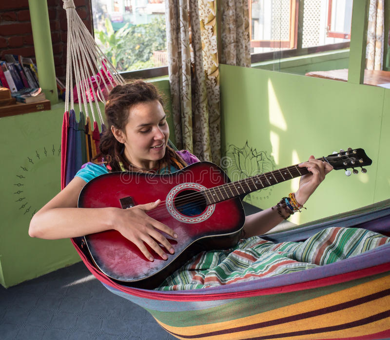 Young woman playing guitar stock photography