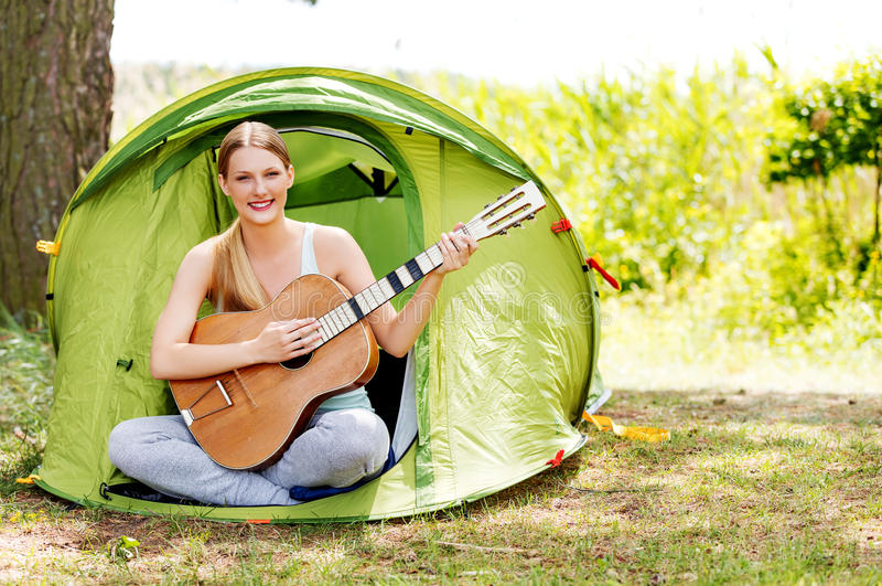 Young woman playing the guitar in a tent on the nature royalty free stock photos