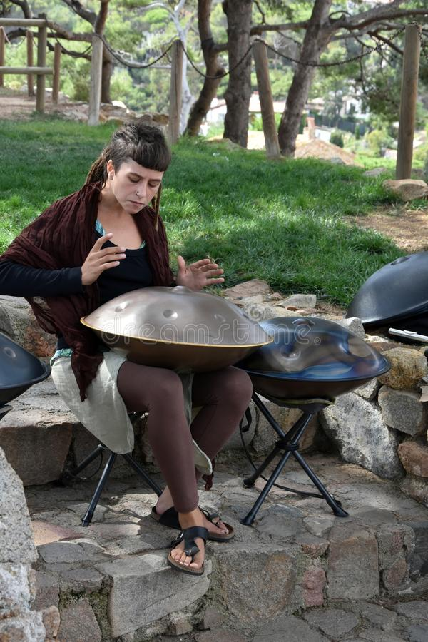 Young woman playing hang instrument. Street musician playing a percussion instrument called Hang. You can play it with with the tips of the fingers, thumbs or