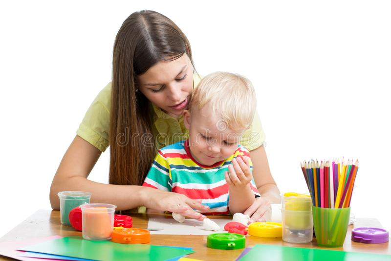 Young woman playing with her boy with plasticine on white background royalty free stock image