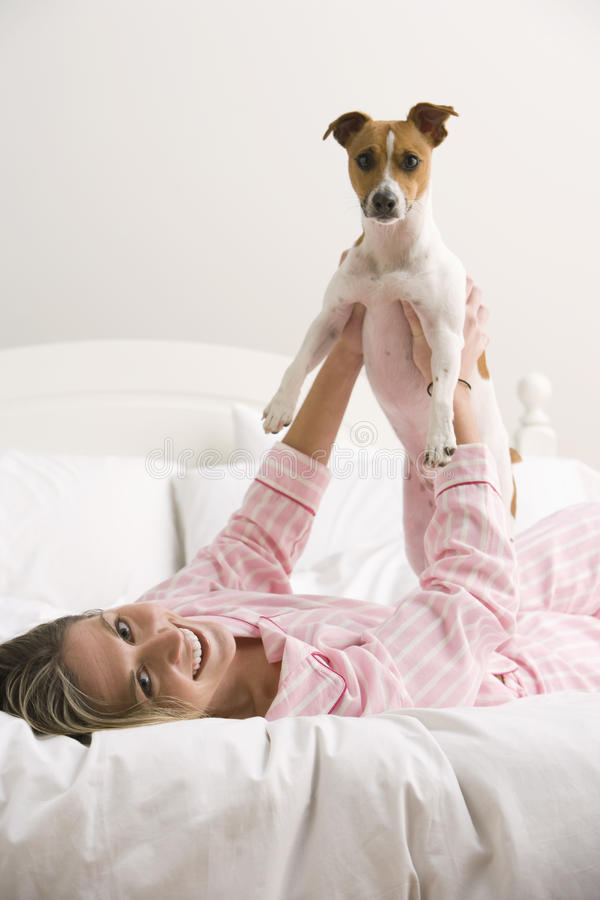 Young Woman Playing With Her Dog On The Bed Stock Photo