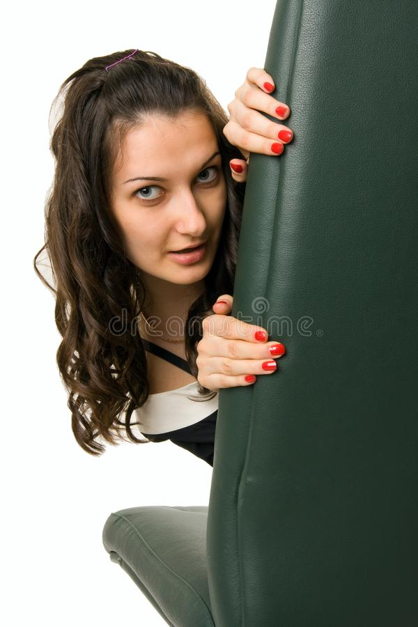 Young woman playing hide-and-seek and looking out