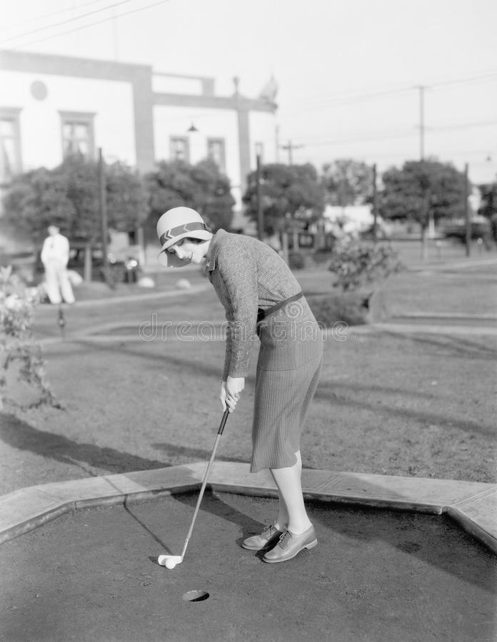 Young woman playing mini golf stock images