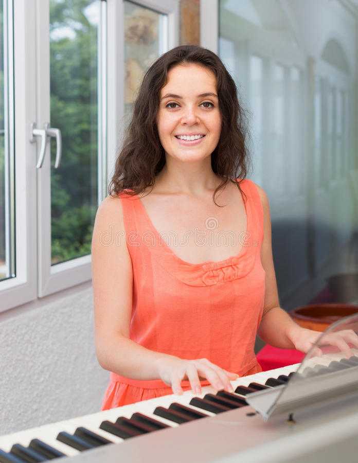 Young woman playing piano at home stock photo
