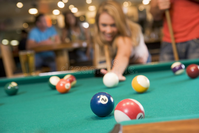 Young woman playing pool in a bar. (focus on pool table stock photography