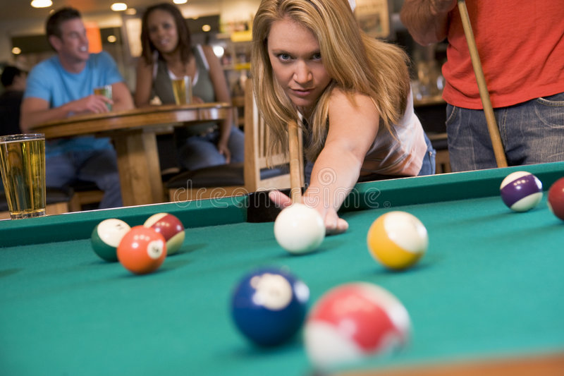 Young woman playing pool in a bar. With people in the background stock photography