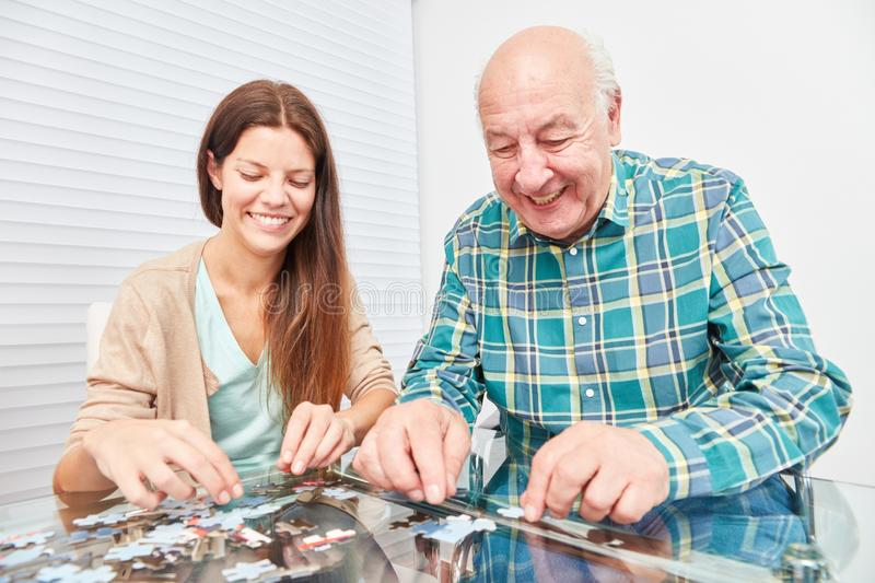 Young woman playing puzzle with senior stock image