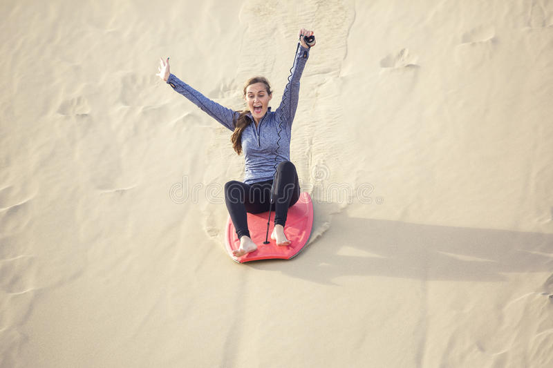 Young Woman Playing in the Sand Dunes Outdoor Lifestyle. An thrilled and excited young woman riding a board down a sand dune hill having fun playing outdoors stock photography