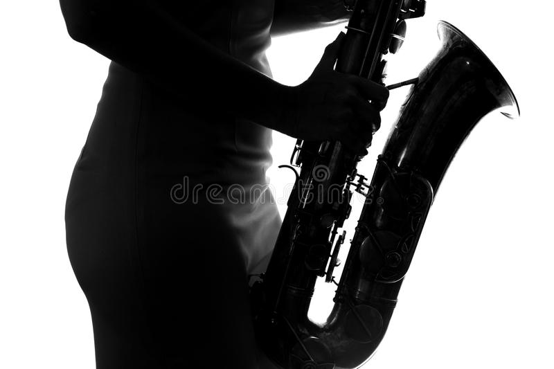 Young woman playing the saxophone stock images
