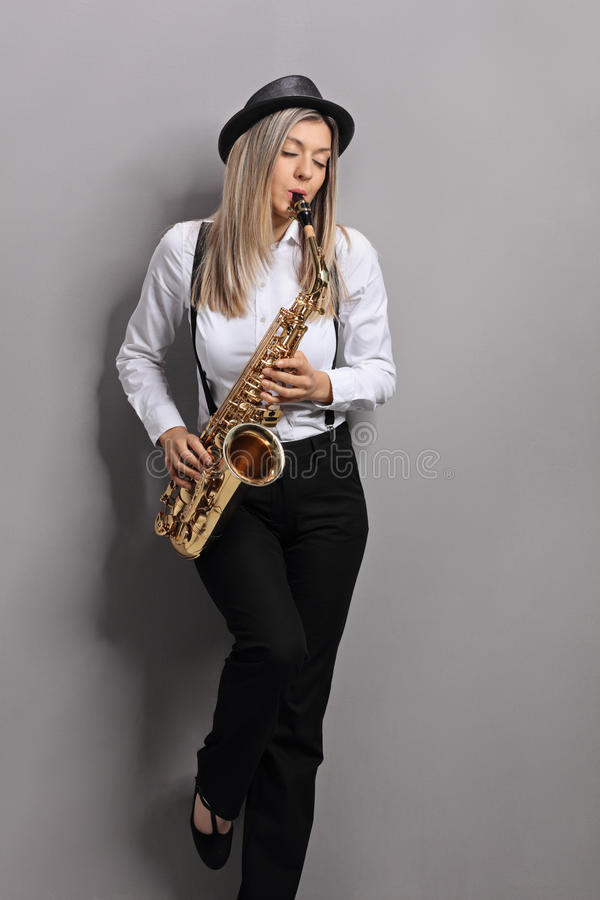 Young woman playing saxophone and leaning against gray wall stock photos