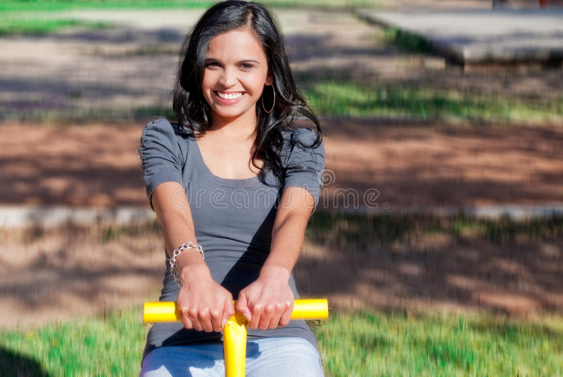 Young woman playing in a seesaw. Young woman smiling and playing in a seesaw at a park royalty free stock photo
