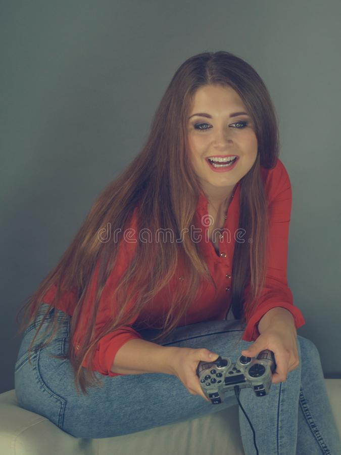 Young woman playing video games. Nerd geek young adult woman playing on the video console holding game pad sitting on sofa. Gaming gamers concept royalty free stock photo