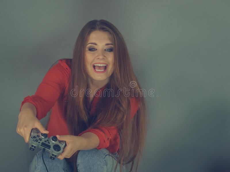 Young woman playing video games. Nerd geek young adult woman playing on the video console holding game pad sitting on sofa. Gaming gamers concept royalty free stock photos