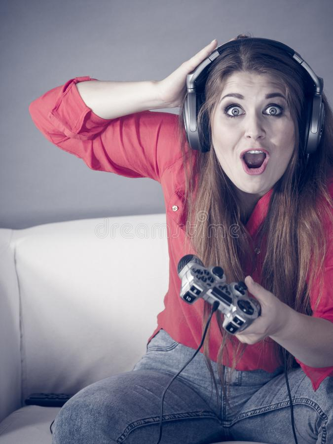 Young woman playing video games. Nerd geek young adult woman playing on the video console holding game pad being shocked Gaming gamers concept royalty free stock photos