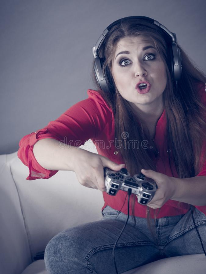 Young woman playing video games. Nerd geek young adult woman playing on the video console holding game pad being shocked Gaming gamers concept stock photography