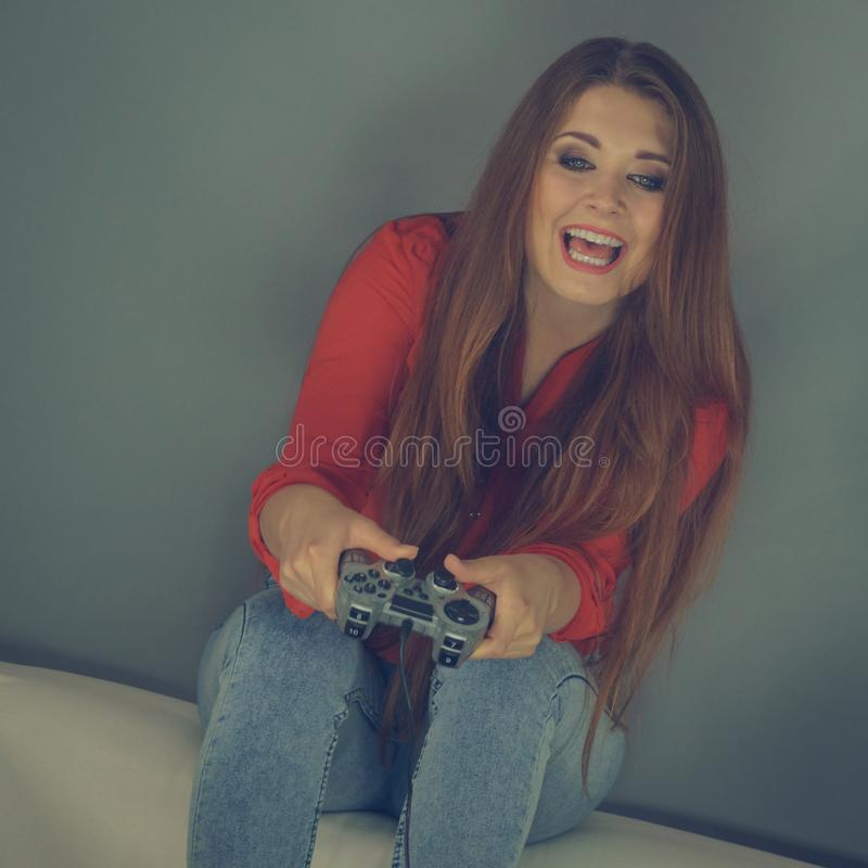 Young woman playing video games. Nerd geek young adult woman playing on the video console holding game pad sitting on sofa. Gaming gamers concept stock photo