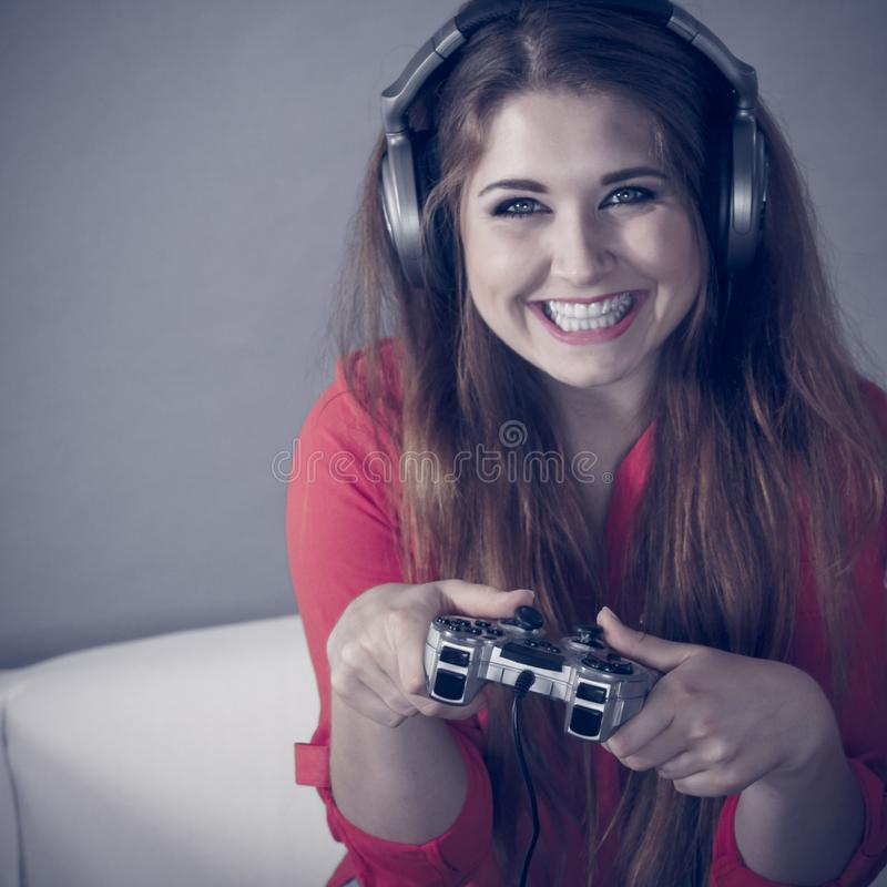 Young woman playing video games. Nerd geek young adult woman playing on the video console holding game pad sitting on sofa. Gaming gamers concept stock photography