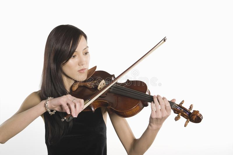 Young Woman Playing Violin. Isolated over white background royalty free stock image