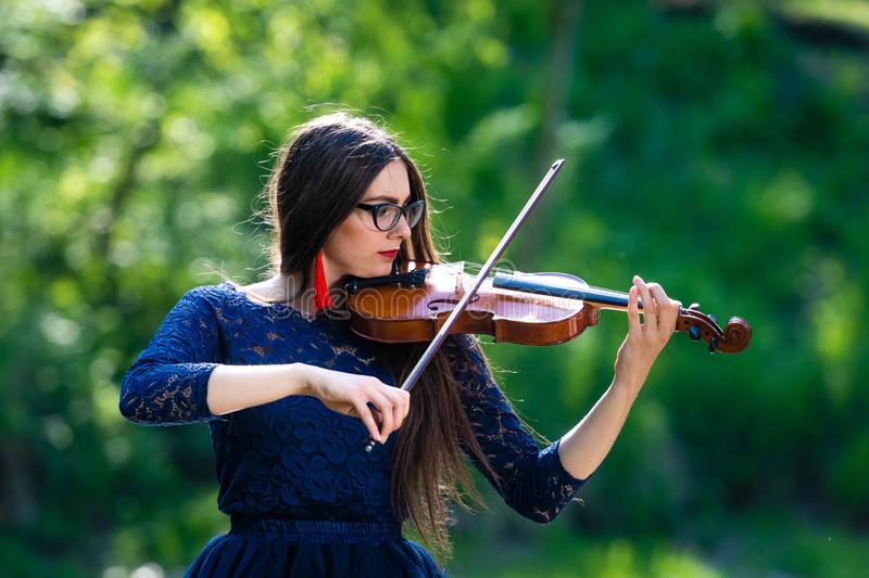 Young woman playing the violin at park. Shallow depth of field - image stock image