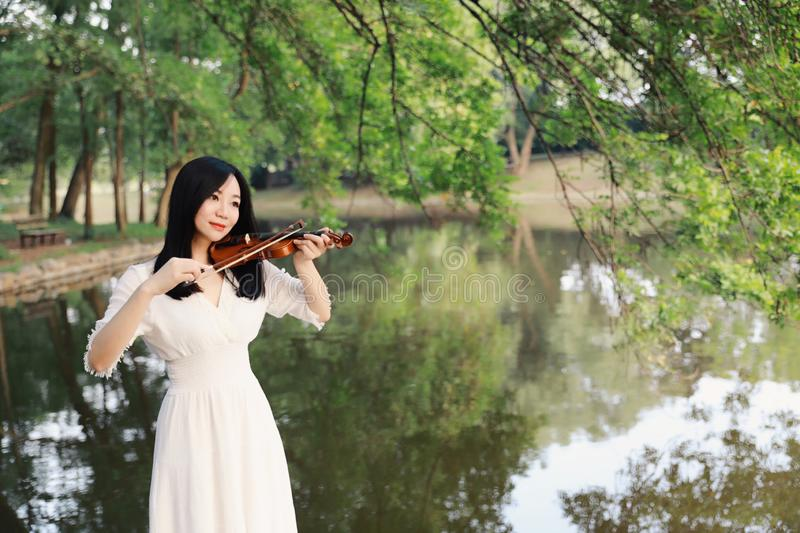 Young woman playing violin ,Silhouette of teenage violin player over sunset on river,lake royalty free stock photography