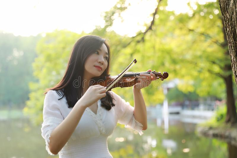 Young woman playing violin ,Silhouette of teenage violin player over sunset on river,lake royalty free stock photos