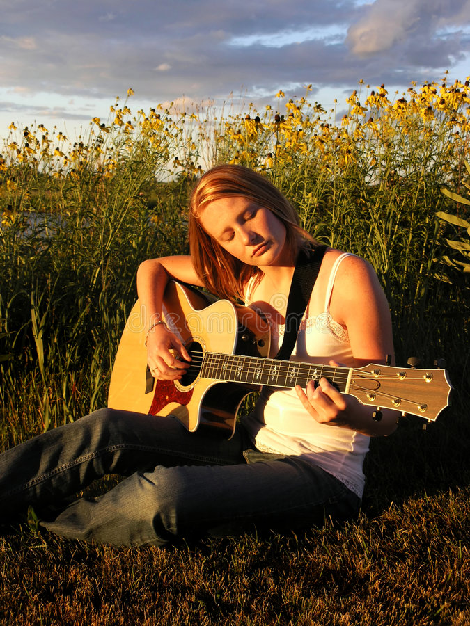 A young woman plays a guitar royalty free stock image