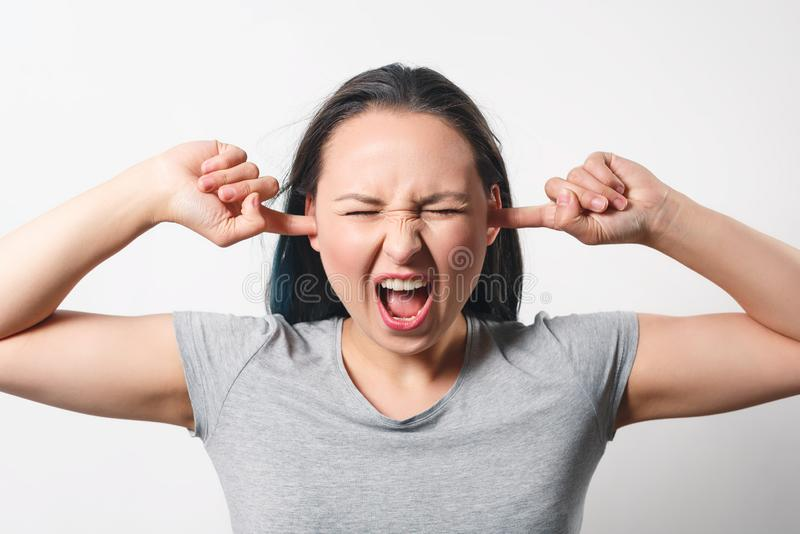 A young woman plugged her ears with her fingers. On white stock photos