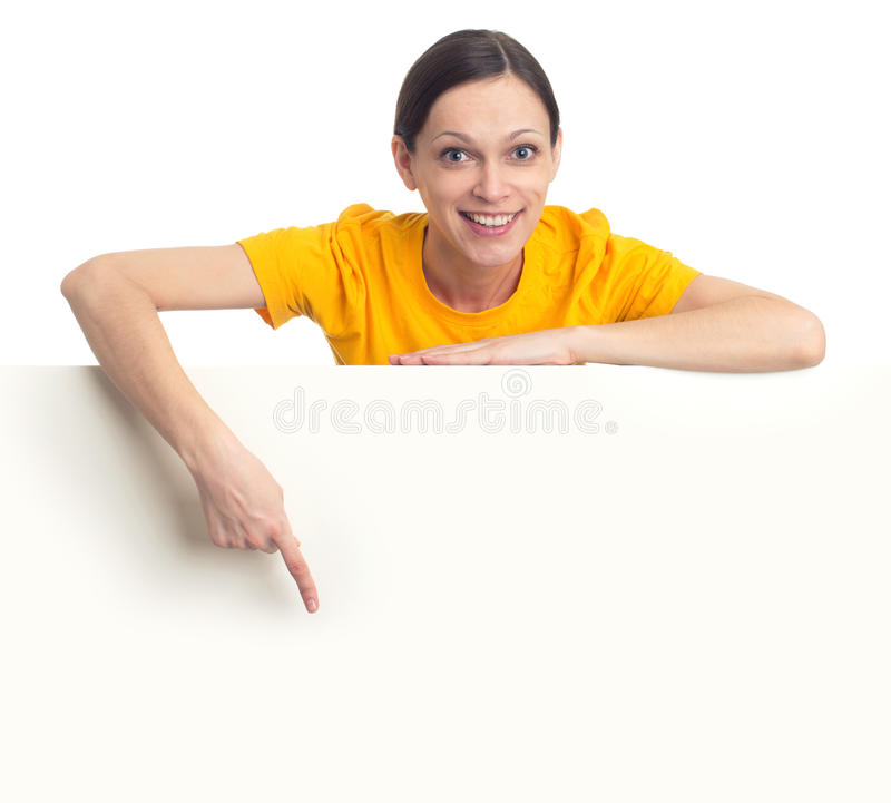 Young woman pointing finger at blank poster. Smiling casual young woman pointing finger at blank poster royalty free stock photos