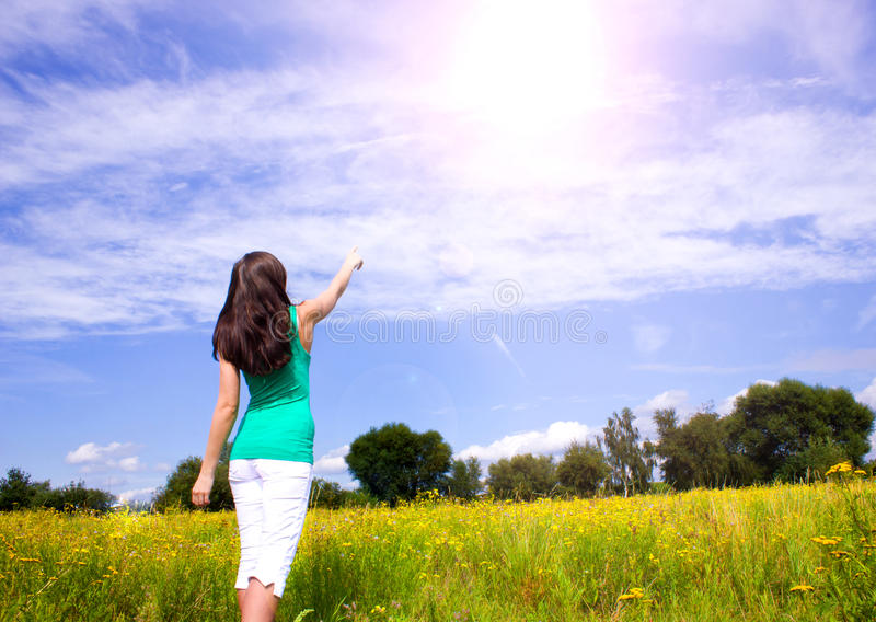 Young woman pointing the finger into the sky royalty free stock images