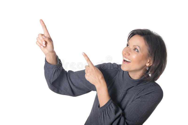 Young woman pointing on something. Against white royalty free stock image