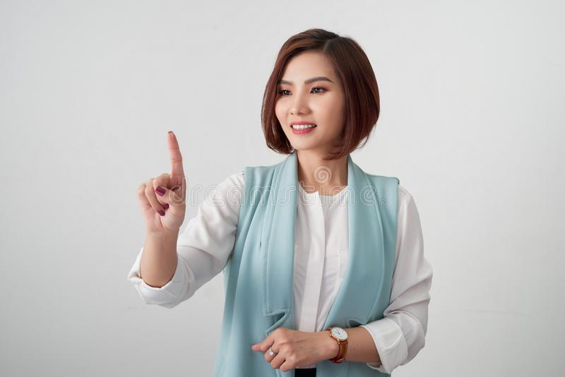Young woman pointing at something on a white background royalty free stock photos