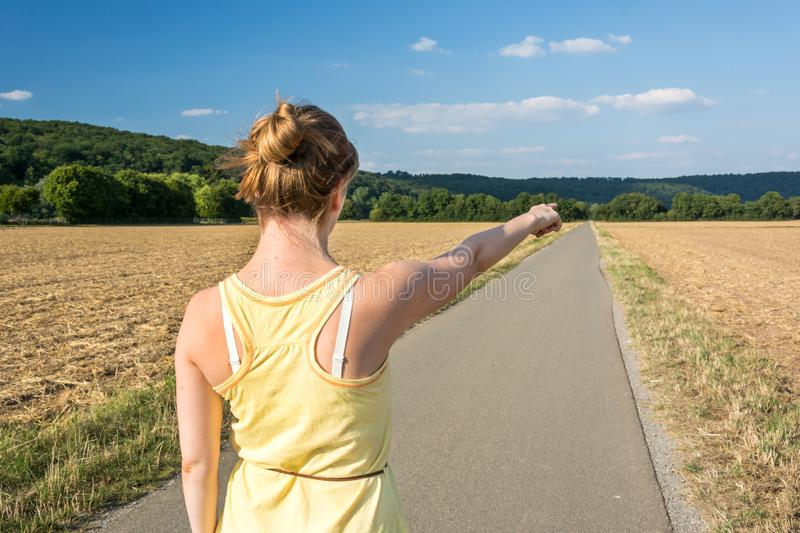 Young woman pointing towards the distance in a rural landscape royalty free stock images