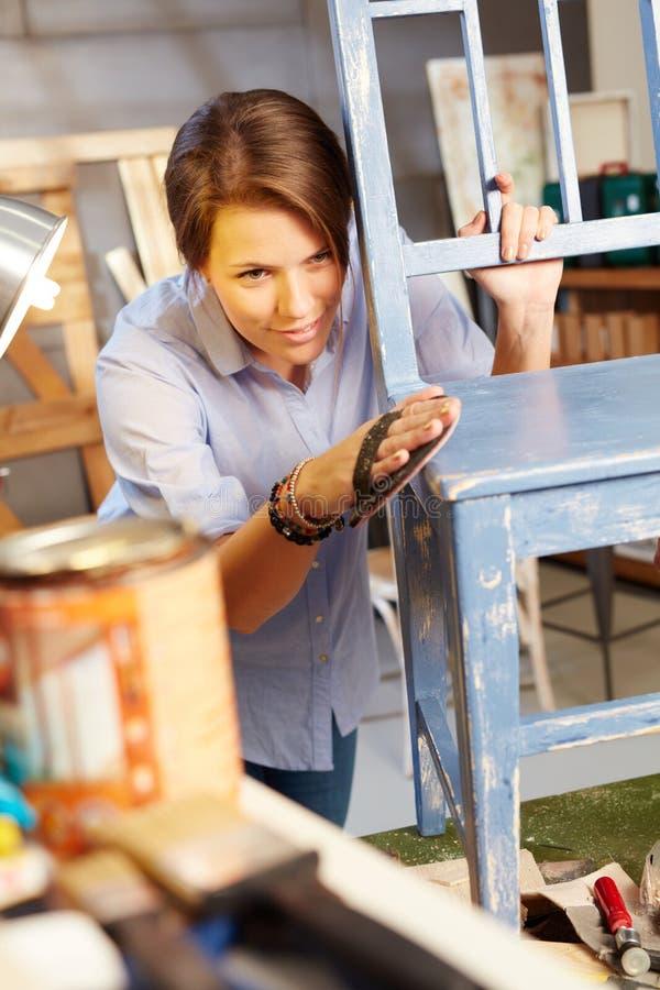 Young woman polishing chair royalty free stock image