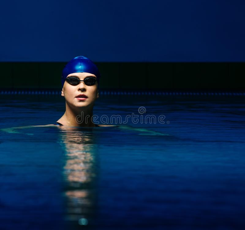 Young woman in pool. Young woman in blue cap and swimming suit in pool stock photos