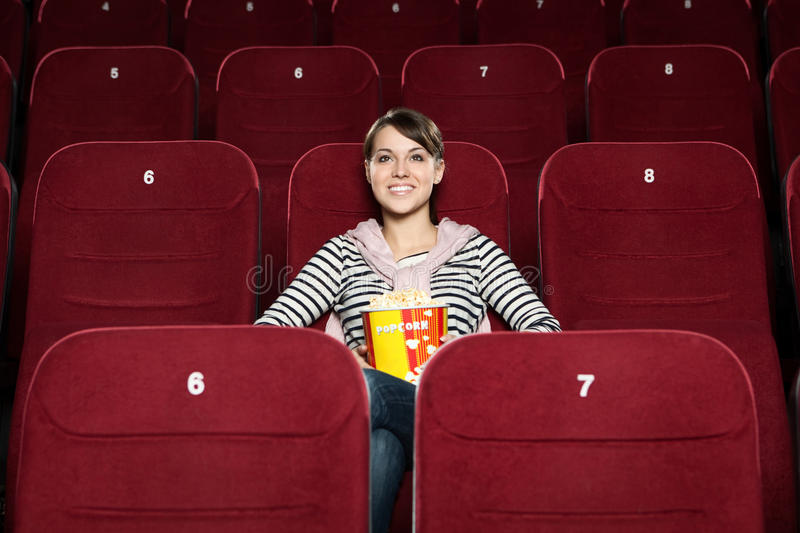 Young woman with popcorn in the movie theater royalty free stock images