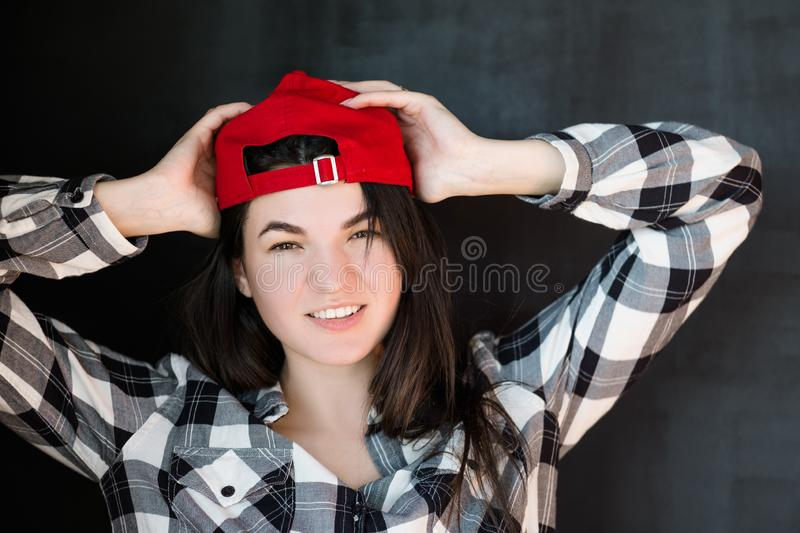 Young woman carefree millennial relaxed smile red. Young woman portrait. Carefree friendly millennial. Red cap casual clothes. Relaxed posture. Warm smile. Hands royalty free stock photo
