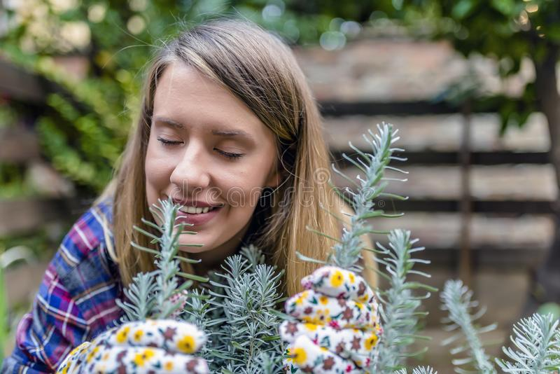 Young Woman Portrait in her Vegetable Garden. woman smelling rosemary. Young Woman Portrait in her Vegetable Garden. Girl smelling the fragrance of a rosemary royalty free stock photos